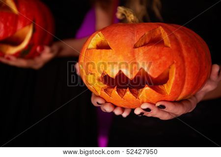 Photo of carved Halloween pumpkin on female palms