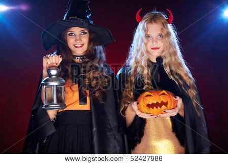 Portrait of two females with lantern and pumpkin looking at camera with smiles