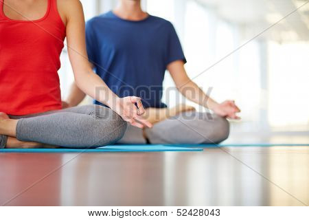 Lower part of slim female and man on background meditating in pose of lotus in gym