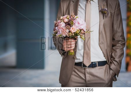 newlywed's hands and wedding bouquet