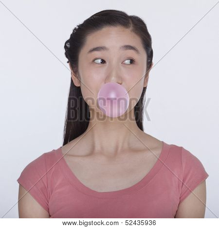 Young playful woman blowing bubble out of bubble gum