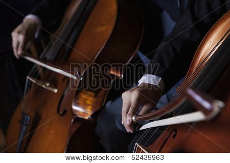 Close-up of midsection of two cellists playing the cello