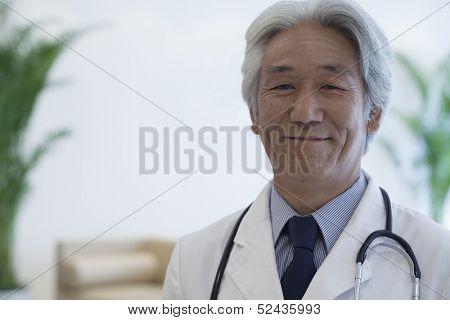 Portrait of mature doctor looking at camera and smiling