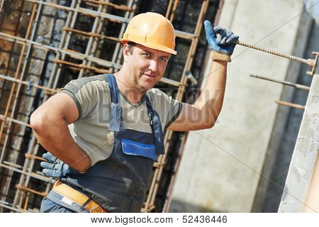 Portrait of builder worker concreter with metal rods bars at framework reinforcement for concrete pouring in construction site