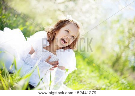 The beautiful little girl, with bush blossoming apple-tree, smil