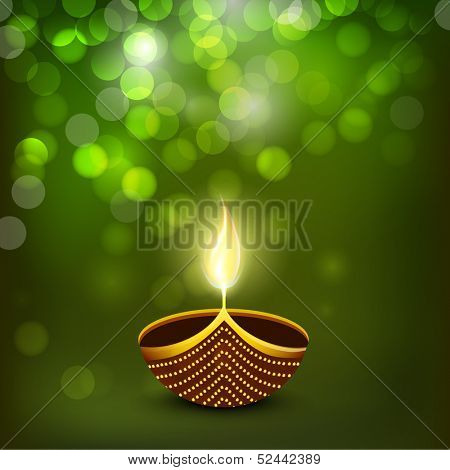 Indian festival of lights Happy Diwali greeting card or background with illuminated oil lit lamp on shiny green background.