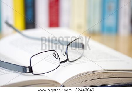 Book with glasses on desk