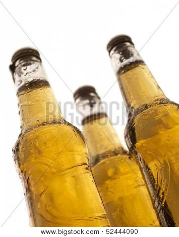three bottles of beer with water drops