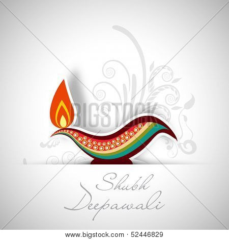 Indian festival of lights, Shubh Deepawali (Happy Deepawali) concept with illuminated colorful oil lit lamp on floral decorated grey background.