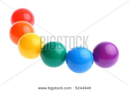 Six Shiny Coloured Plastic Toy Balls In Row Isolated On White Copy Space And Room For Text