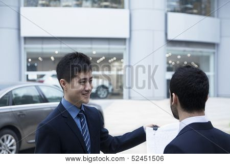 Car salesman selling a car to a young businessman