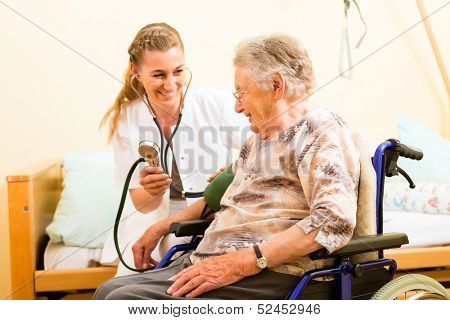 Young nurse and female senior in nursing home, the blood pressure is going to be measured