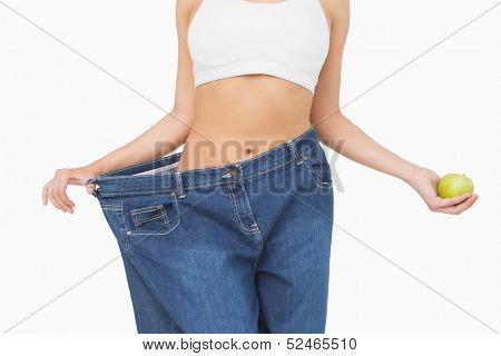 Mid section of slim woman wearing too big jeans holding an apple on white background
