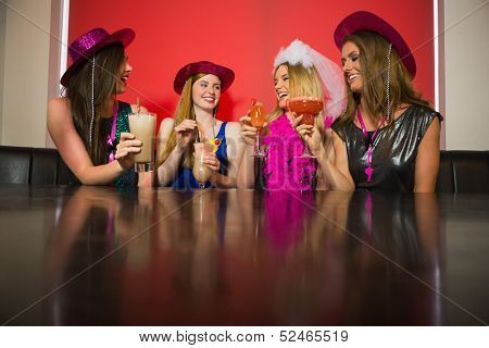 Attractive friends at a hen night drinking cocktails in a nightclub