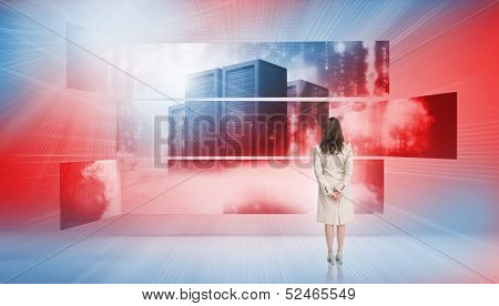 Rear view of businesswoman looking at screens showing server towers in blue red light