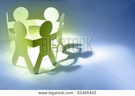 Team of paper doll people in circle holding hands. Advertising copy space to right