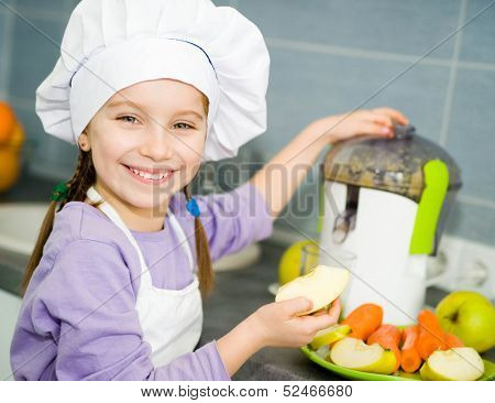 smily pretty girl making fresh apple juice with a juice extractor