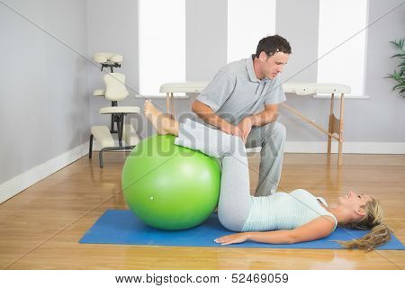 Physiotherapist checking patient doing exercise with exercise ball in bright room