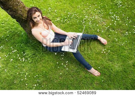 Beautiful woman leaning against a tree using her notebook smiling at camera