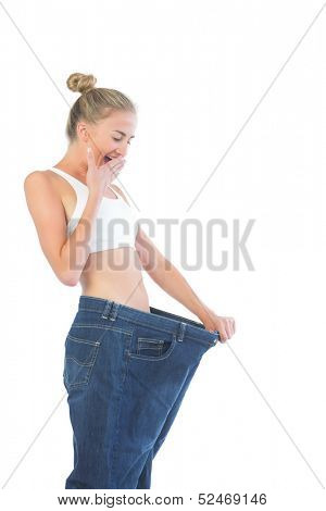Confident laughing blonde wearing too big trousers on white background