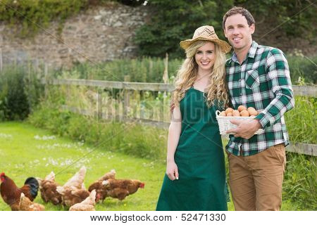 Young couple posing on a lawn holding a basket filled with eggs with chickens behind