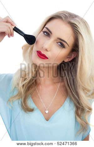 Thoughtful blonde model in blue dress applying make up on white background