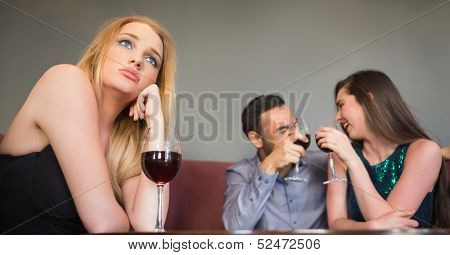 Blonde woman feeling jealous of two people are flirting beside her in a nightclub