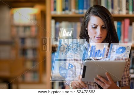 Pretty student working on her futuristic tablet in a library
