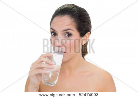 Content bare brunette drinking glass of water on white background