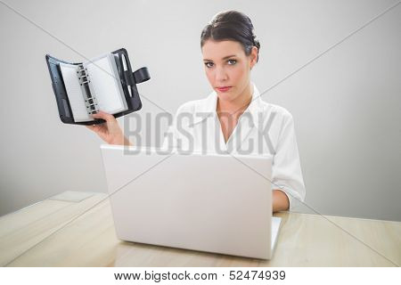 Serious businesswoman working on laptop holding datebook in bright office