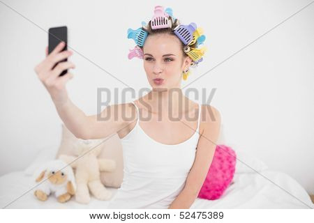 Funny natural brown haired woman in hair curlers taking a picture of herself with mobile phone in bright bedroom