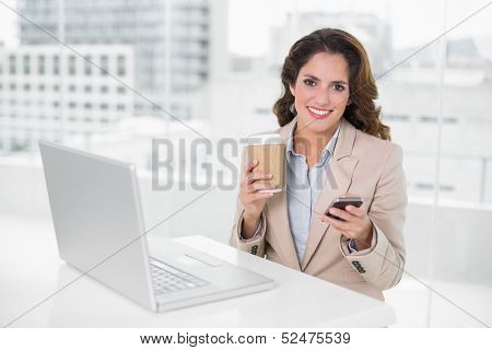 Cheerful businesswoman holding disposable cup and smartphone in bright office