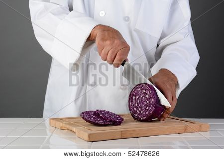 A chef cutting a head of red cabbage on a wood cutting board. Horizontal format on a light ot dark gray background. Man is unrecognizable.