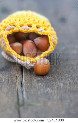 Yellow Bag With Hazelnut On The Old Board