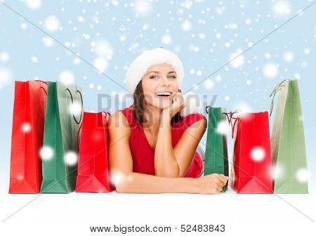 shopping, sale, gifts, christmas, x-mas concept - smiling woman in red shirt and santa helper hat with shopping bags