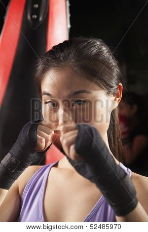 Portrait of determined female boxer in fighting stance