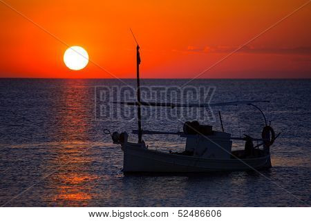 Ibiza sunset  view and menorquina fisherboat from Formentera orange sky