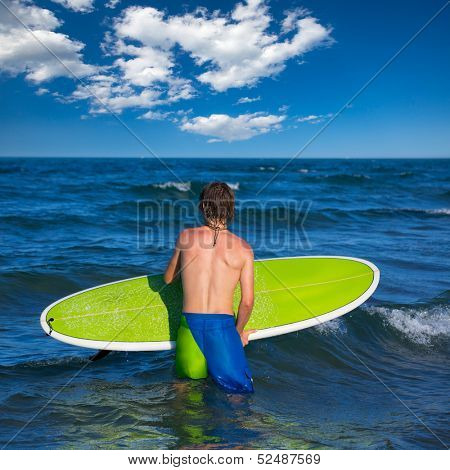 boy surfer waiting for the waves on the blue beach