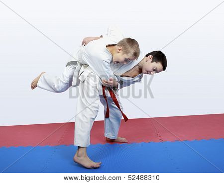 Boy athlete with a red sash makes hip throw