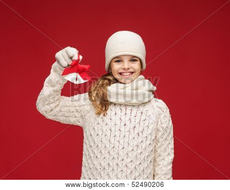 christmas, x-mas, winter, happiness concept - smiling girl in hat, muffler and gloves with jingle bells