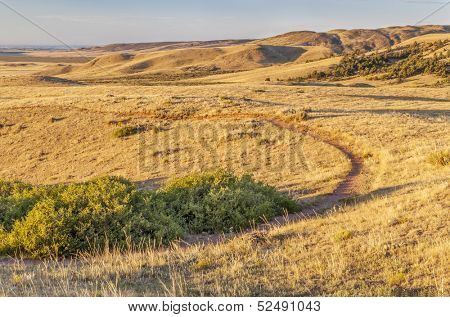 sunrise illuminates a trail through rolling prairie at foothills of Rocky Mountains in Colorado - Soapstone Open Space near Fort Collins