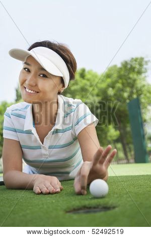 Smiling young woman flicking the golf ball into the hole