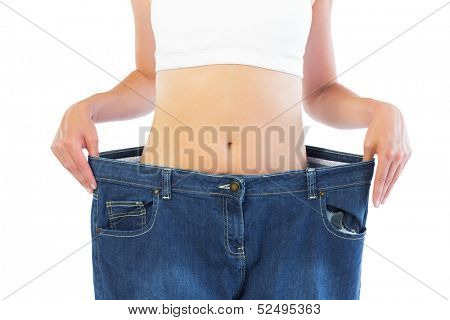 Close up of confident thin blonde wearing too big trousers on white background