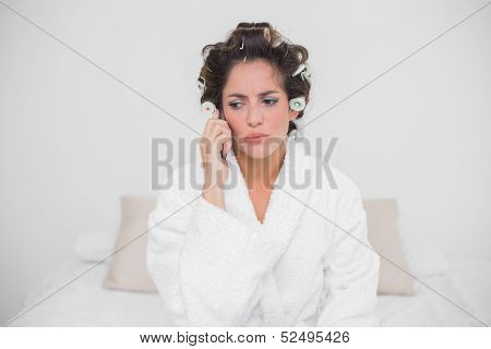 Upset natural brunette phoning and sitting on bed