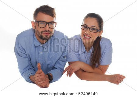 Nerdy looking couple wearing blue shirts and thick frame glasses looking at camera while leaning forward on a white background