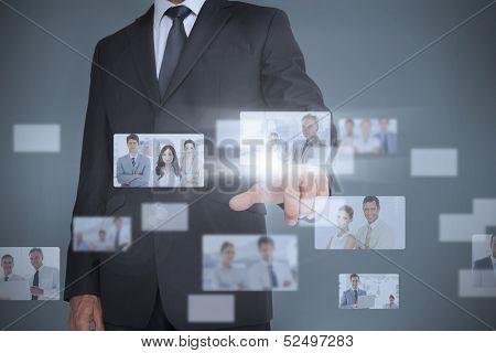 Businessman showing futuristic interface of coworkers posing