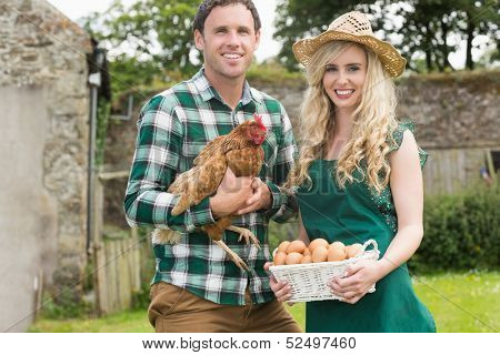 Smiling young couple holding chicken and basket of eggs in their garden