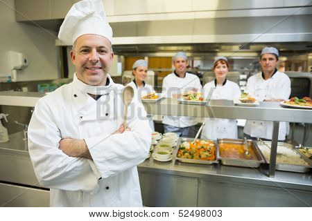Experienced head chef posing proudly in a modern kitchen with his team in the background