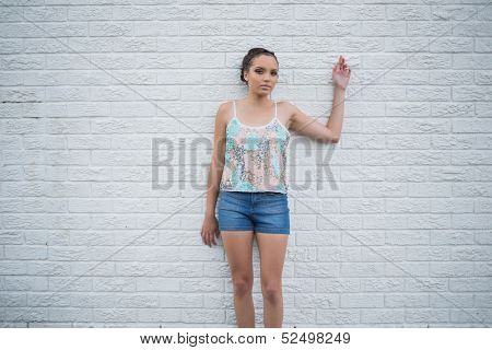 Sexy woman posing and looking at camera in front of a white wall
