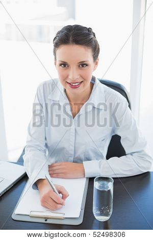 Cute stylish brunette businesswoman taking notes and looking at camera in bright office